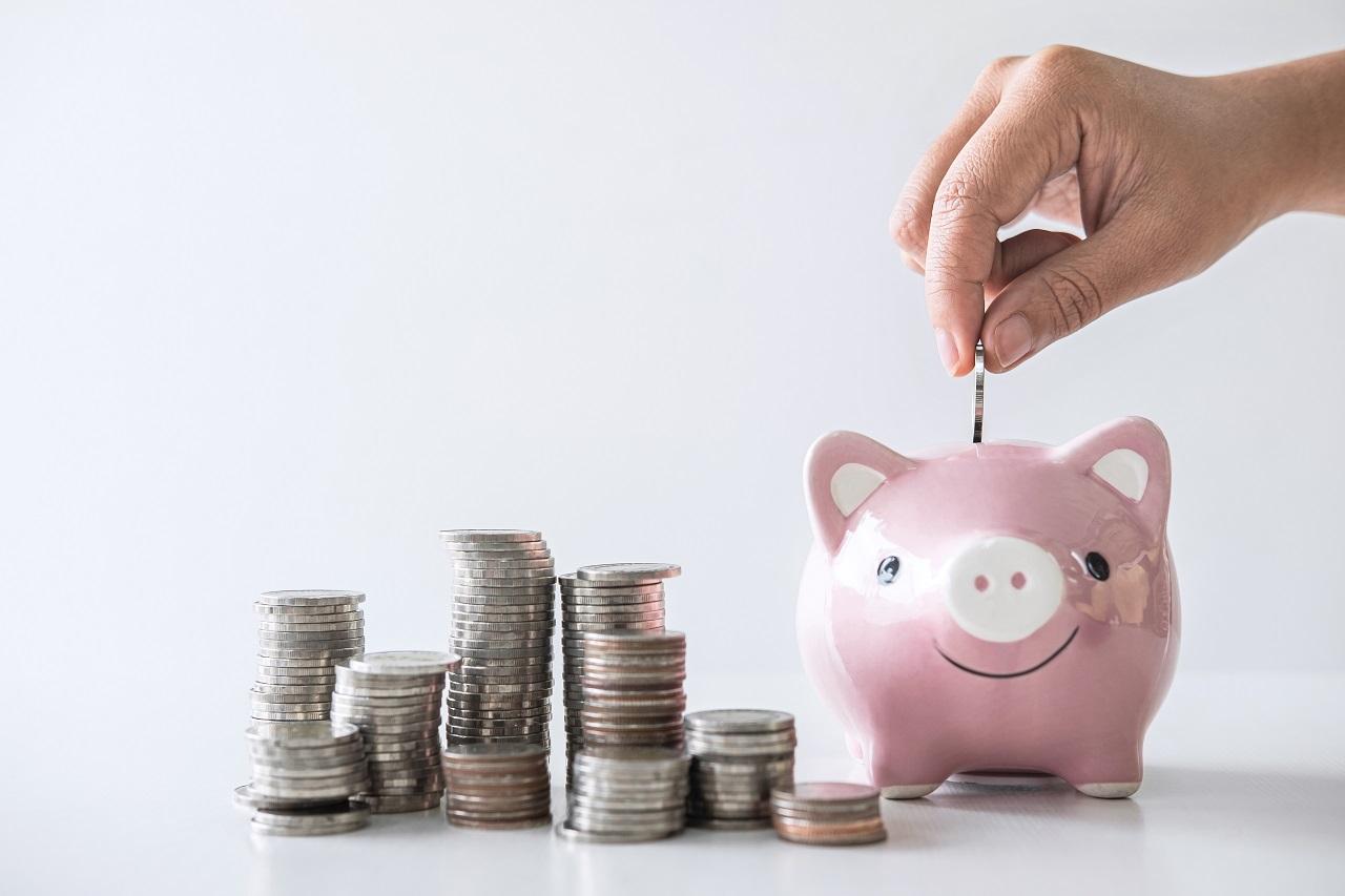 A hand putting coins into a piggy bank
