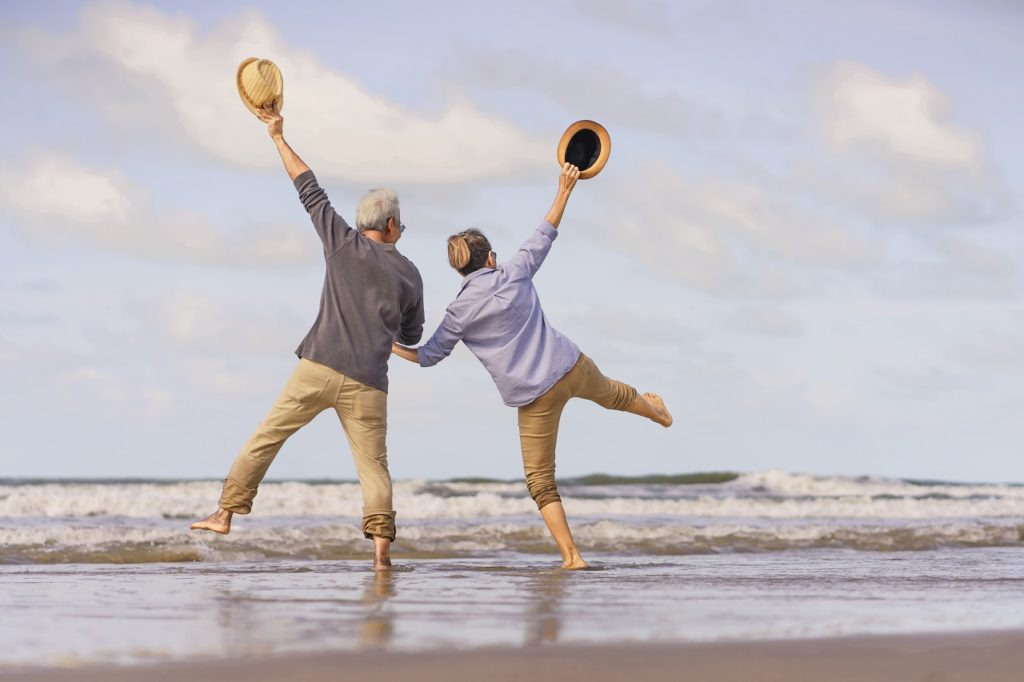A senior Asian couple jumping at the beach after their retirement