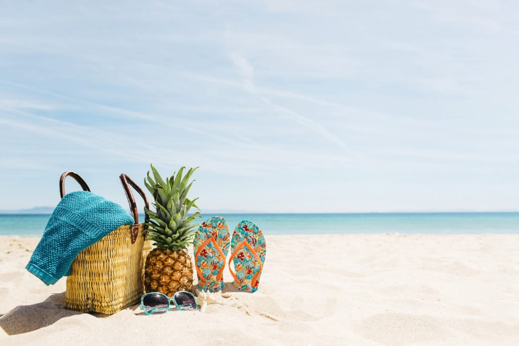 Travel bag, slippers, and a pineapple on a beach in Cagayan de Oro