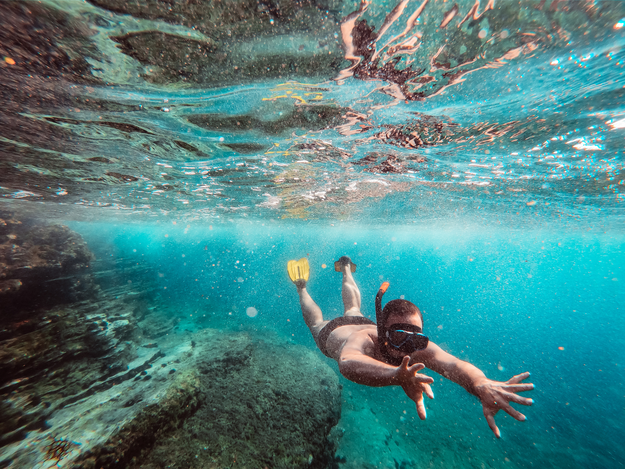 An underwater picture of a man snorkeling in a beach