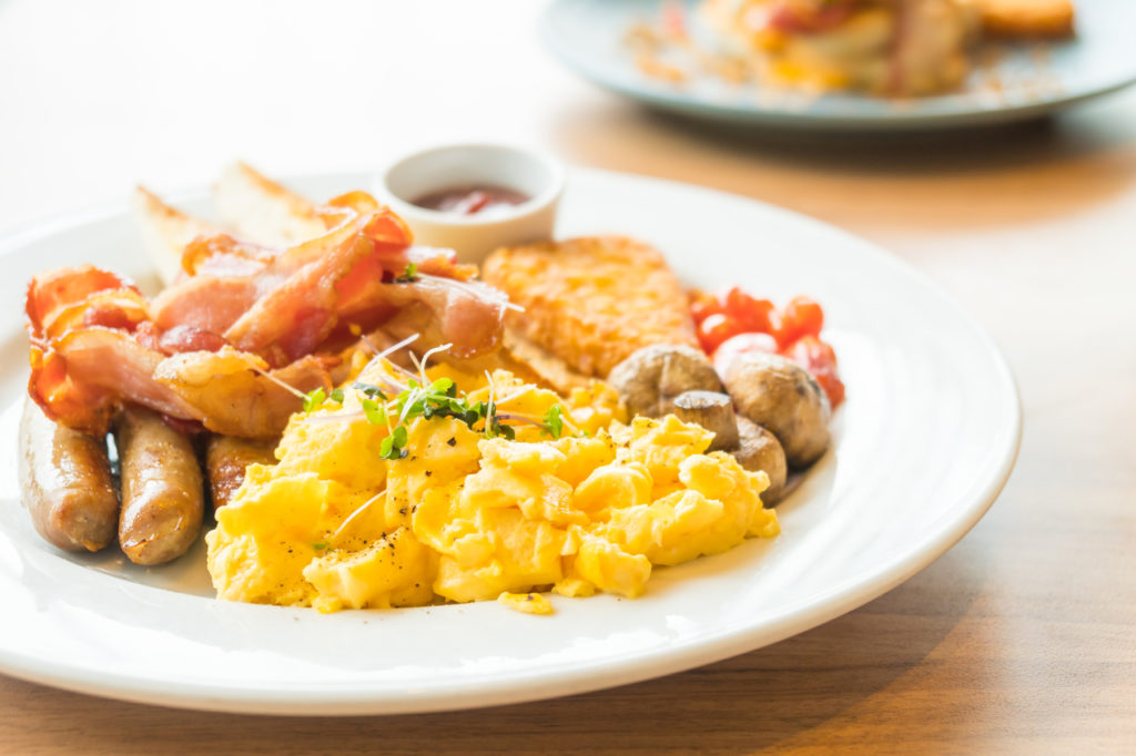 A breakfast plate with eggs, bacon, sausages