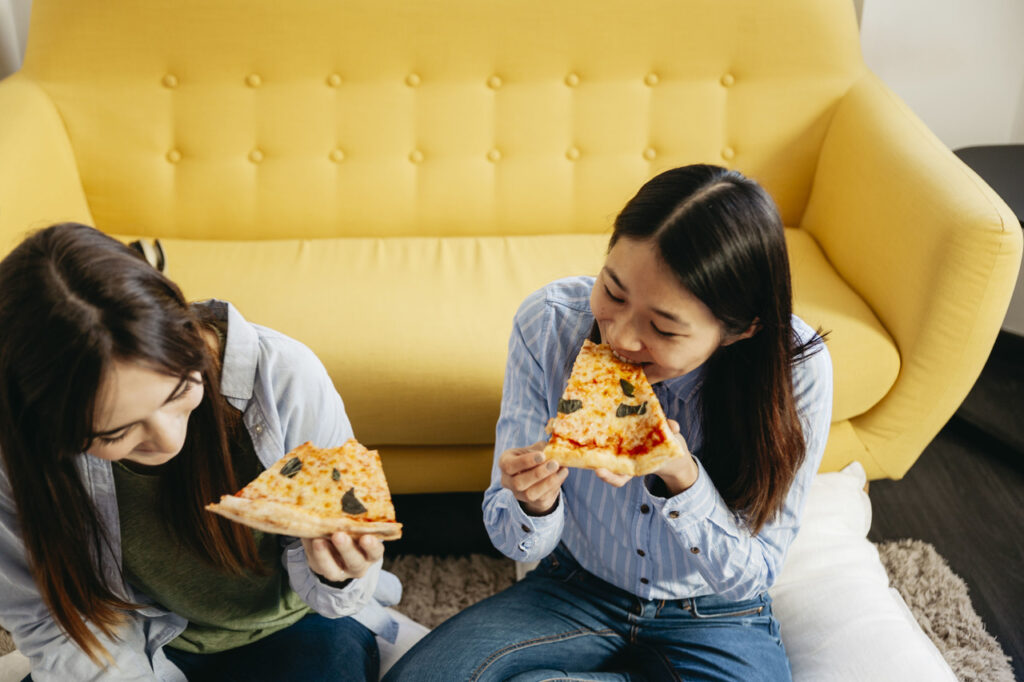 Two women eating pizza at home