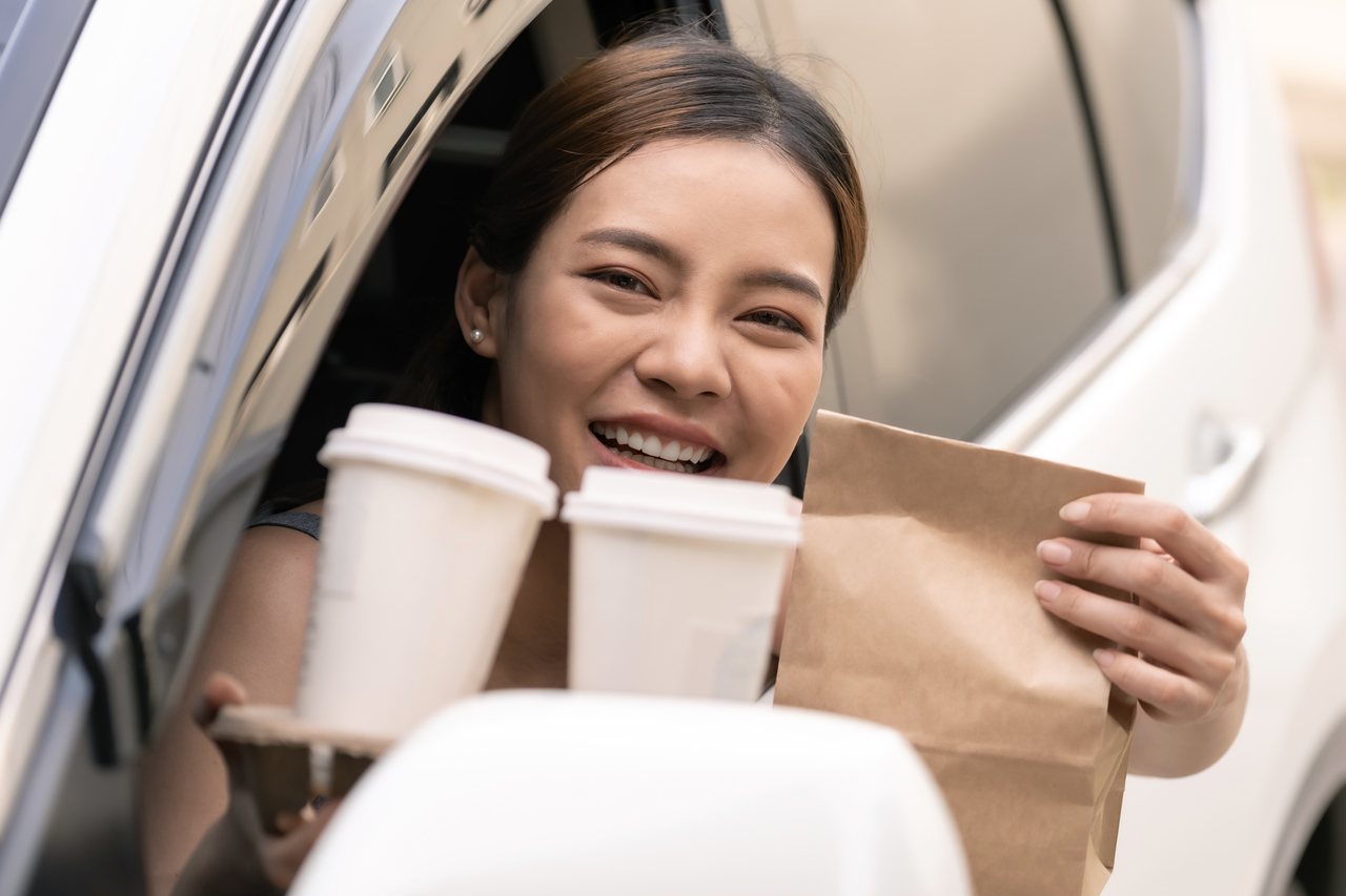 A woman holding take out in a car