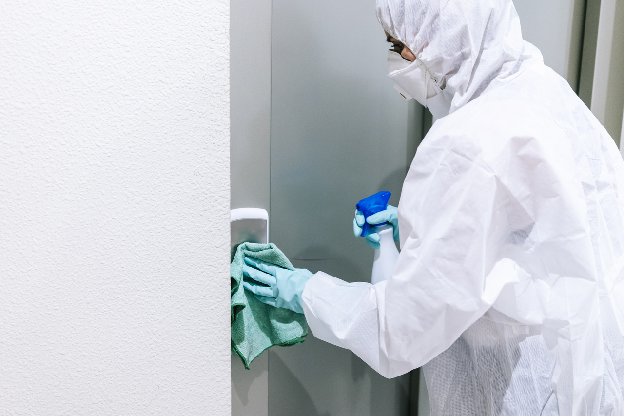 A person disinfecting a doorknob