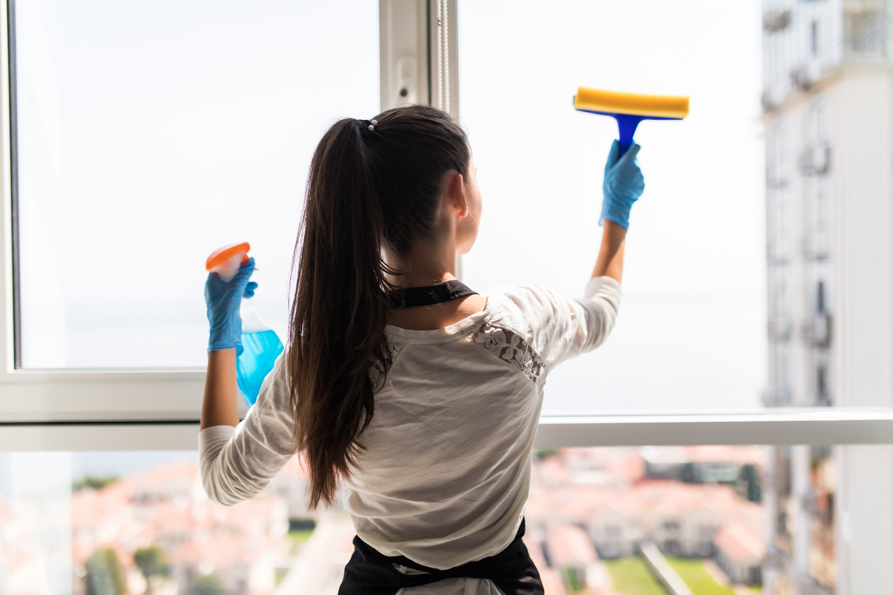 A woman disinfecting her window